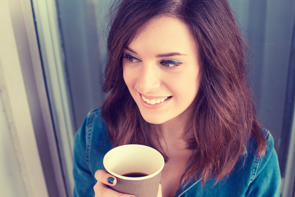 Smiling woman drinking coffee outdoors holding paper cup