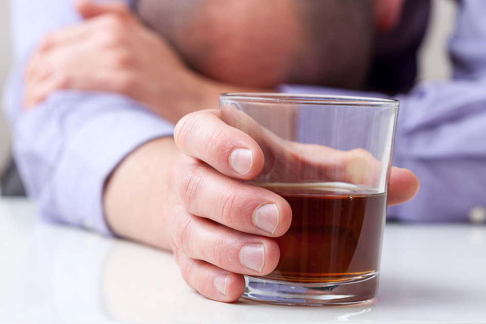 A closeup of a depressed alcoholic holding a glass of whiskey