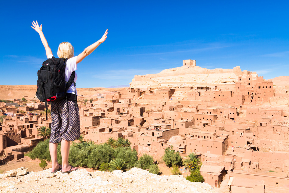 Adventurous woman arms reised in front of Ait Benhaddou, fortified city, kasbah or ksar, along the former caravan route between Sahara and Marrakesh in present day Morocco.